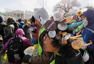 Demonstrators march past the White House during a rally against the Keystone XL pipeline in Washington