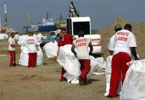Inmates from a La Fourche parish jail on a work release program fill giant sandbags in Port Fourchon